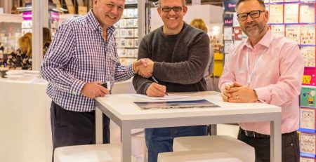 Operations Director Chris Wilcox offering a handshake as the contract is signed with Product Group Director Nick Adsett observing. The Great British Card Company.